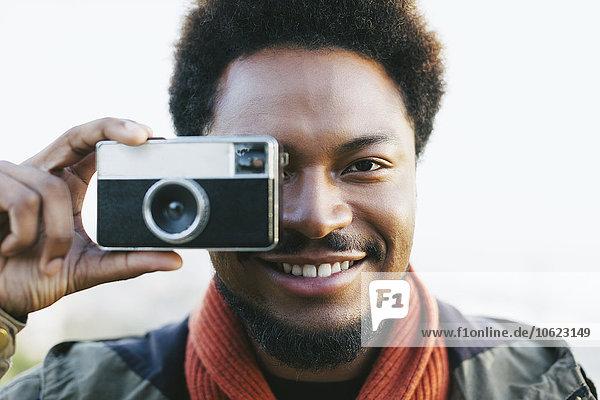 Porträt eines lächelnden jungen Mannes mit alter Kamera