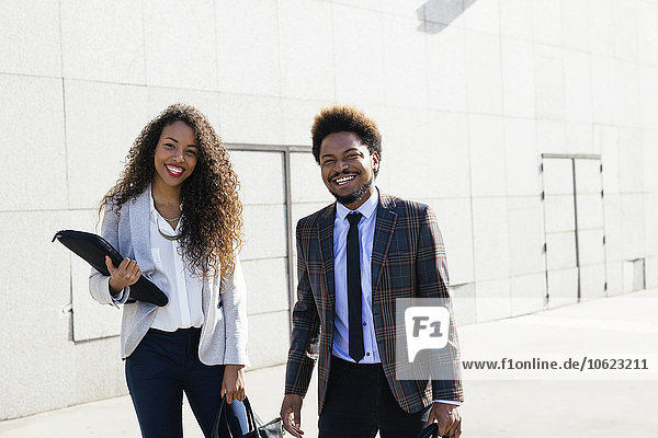 Portrait of two smiling young business people outdoors
