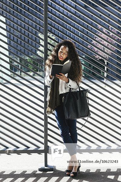 Junge Frau beim Schreiben in einem Notizbuch im Freien