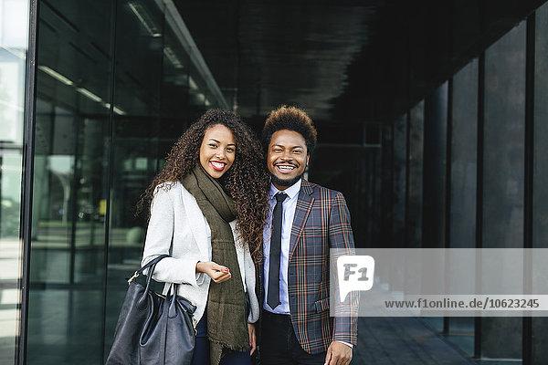 Porträt von zwei lächelnden jungen Geschäftsleuten im Freien