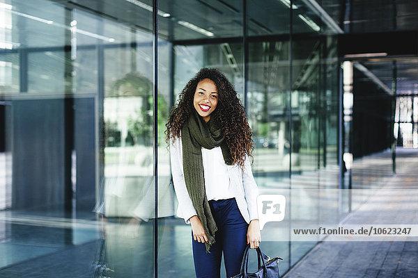 Porträt einer lächelnden jungen Frau  die sich gegen die Glasfront lehnt.
