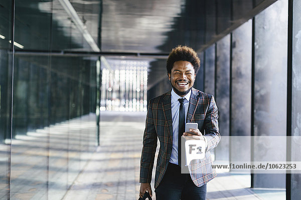 Lachender junger Geschäftsmann mit Handy im Freien