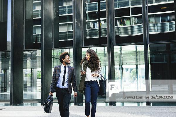 Zwei junge Geschäftsleute  die im Freien spazieren gehen.