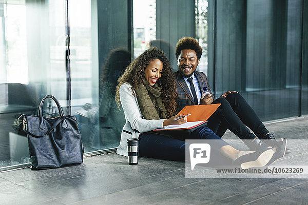 Zwei lächelnde junge Geschäftsleute sitzen mit Akte auf dem Boden.
