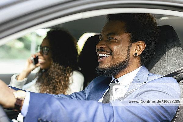 Porträt eines lächelnden Geschäftsmannes im Auto mit seinem Kollegen