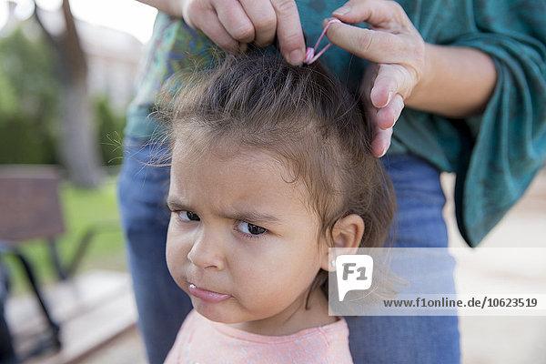 Mutter fesselt die Haare ihrer kleinen Tochter  Nahaufnahme
