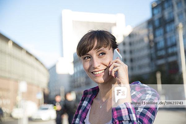 Deutschland  Berlin  Portrait einer jungen Frau beim Telefonieren mit dem Smartphone