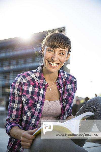 Porträt der lächelnden jungen Frau mit Buch in der Dämmerung