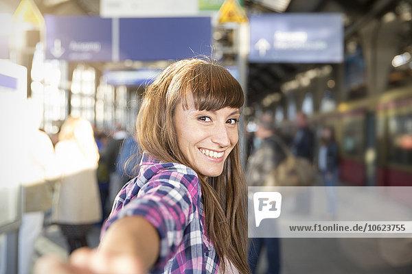 Deutschland  Berlin  Porträt einer lächelnden jungen Frau  die am Bahnsteig Händchen hält