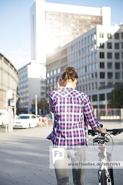Deutschland  Berlin  Rückansicht einer jungen Frau mit Fahrrad