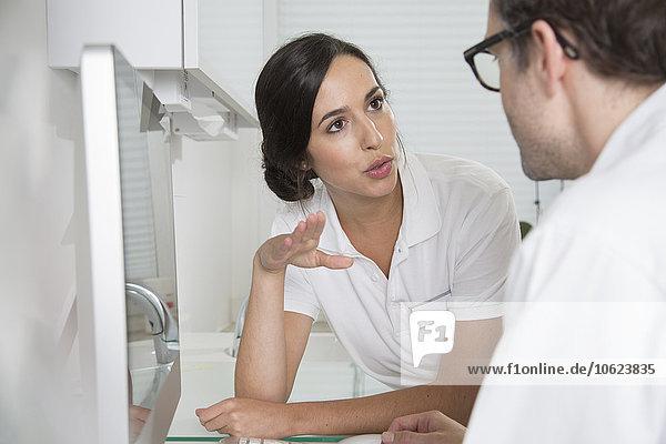 Zwei Ärzte am Schreibtisch diskutieren über