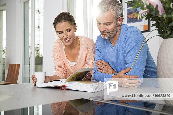 Paar lehnt sich auf Küchenblock und schaut auf Buch