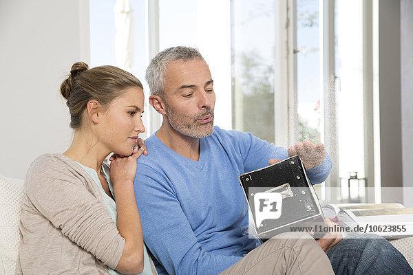 Paar zu Hause beim Betrachten alter Fotos