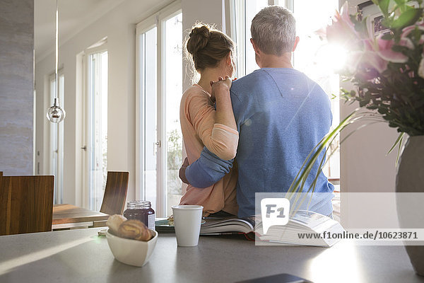 Paar in der Küche mit Blick aus dem Fenster  Rückansicht