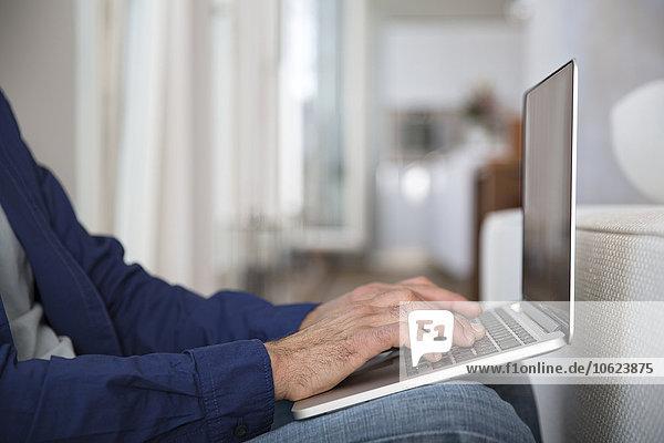 Erwachsener Mann  der von zu Hause aus mit dem Laptop arbeitet