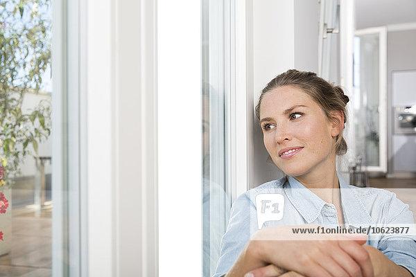 Junge Frau am Fenster sitzend  Knie umarmend