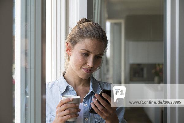 Junge Frau am Fenster stehend mit Smartphone und Kaffeetasse