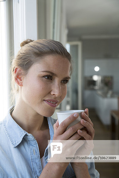 Junge Frau am Fenster stehend  Kaffee trinkend