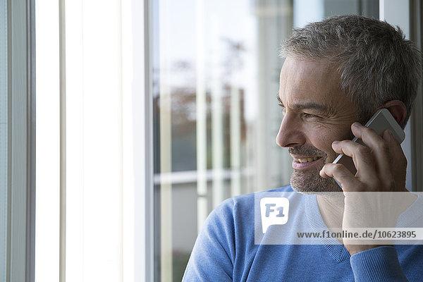 Erwachsener Mann  der von zu Hause aus mit dem Smartphone arbeitet