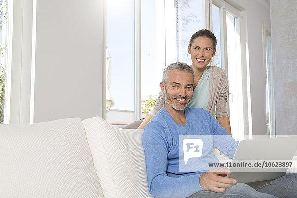 Paar entspannen auf der Couch zu Hause mit dem Laptop