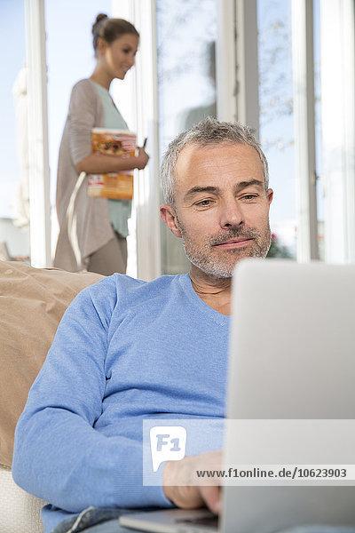 Mann auf Couch sitzend mit Laptop  Frau im Hintergrund