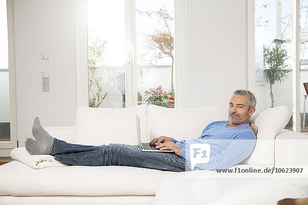Erwachsener Mann zu Hause  sitzend auf der Couch  mit Laptop