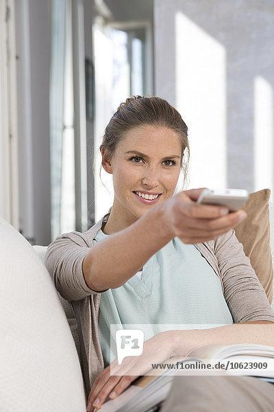 Junge Frau sitzend auf der Couch mit Buch  ferngesteuert