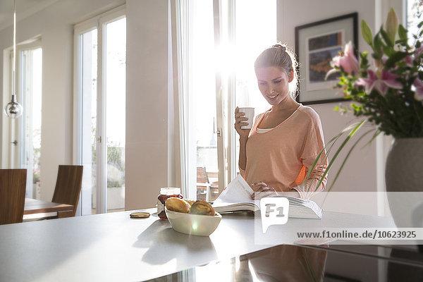 Junge Frau in der Küche beim Frühstück in der Küche  Blättern im Buch