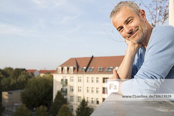 Erwachsener Mann auf dem Balkon  der die Aussicht genießt.