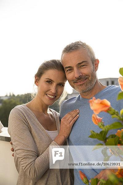 Glückliches Paar  das auf dem Balkon steht  Arme um sich herum.