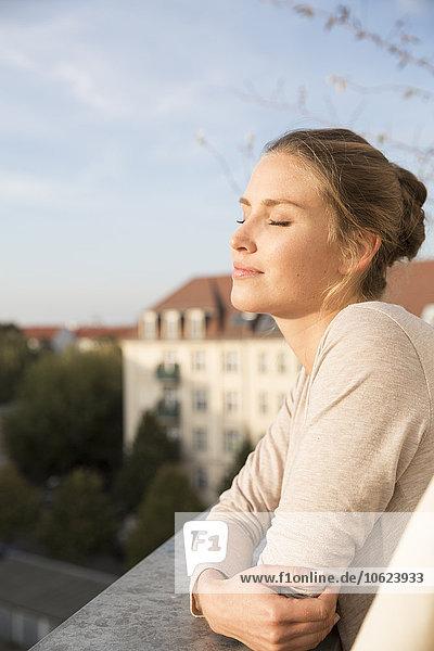 Junge Frau auf dem Balkon  die die Aussicht genießt
