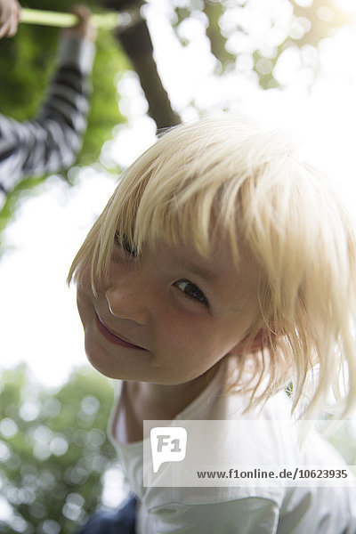 Porträt eines lächelnden blonden Mädchens im Freien