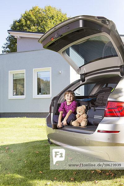 Lächelndes Mädchen mit Teddybär-Autostiefel vor dem Haus