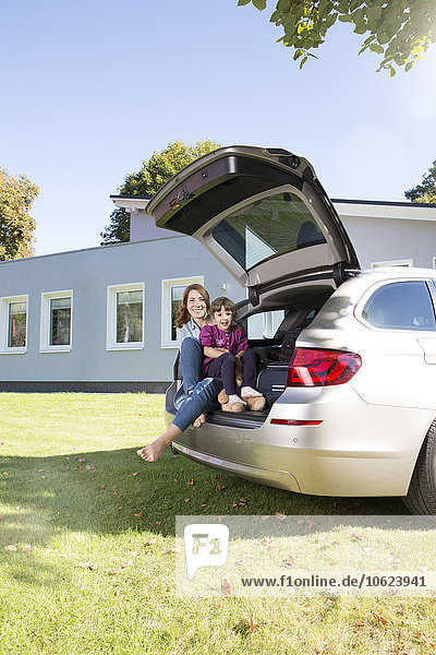 Happy mother and daughter in car boot in front of house