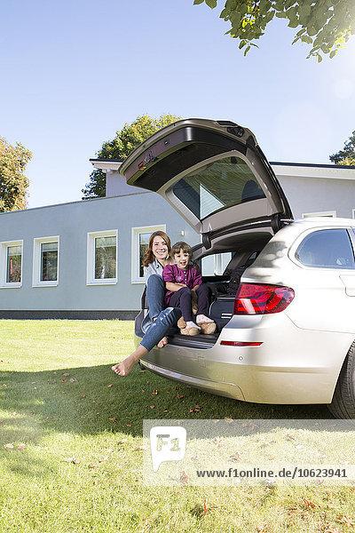 Glückliche Mutter und Tochter im Kofferraum vor dem Haus