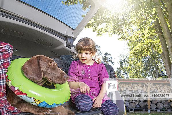 Mädchen im Kofferraum mit Hund mit schwebendem Reifen