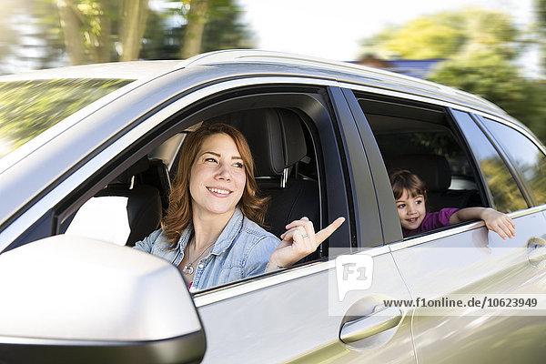 Frau fährt Auto mit Mädchen auf dem Rücksitz