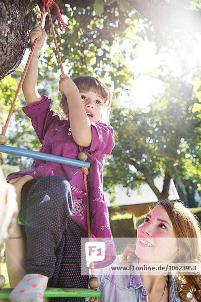 Mutter beobachtet Tochter auf Strickleiter im Garten