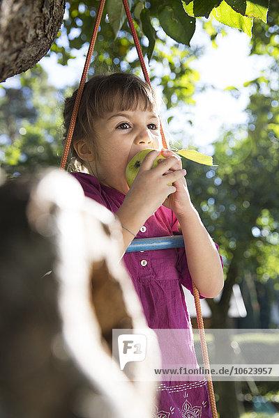 Mädchen beim Essen eines Apfels auf der Strickleiter im Garten