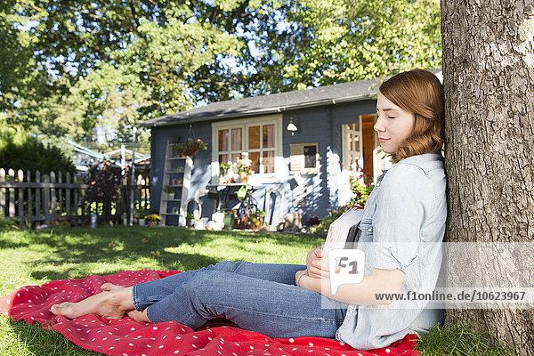 Junge Frau hält Buch zum Entspannen im Garten