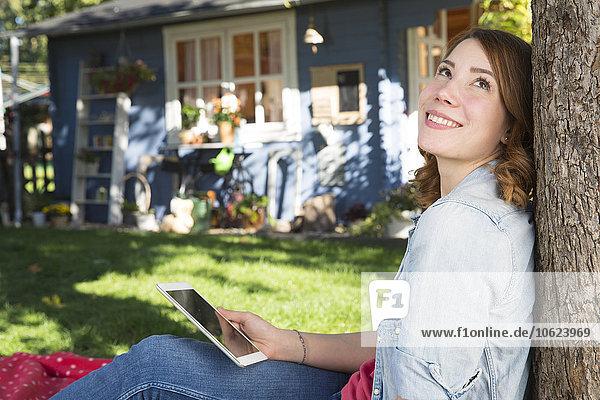 Junge Frau mit digitalem Tablett zum Entspannen im Garten