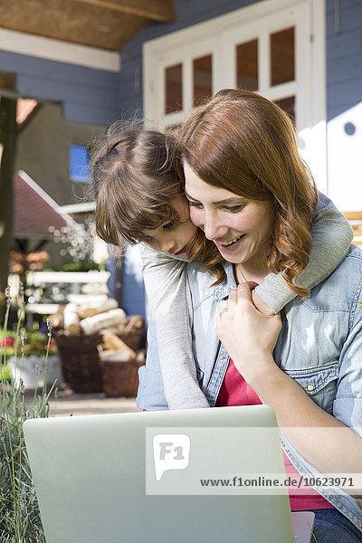 Mutter und Tochter schauen auf den Laptop auf der Gartenterrasse
