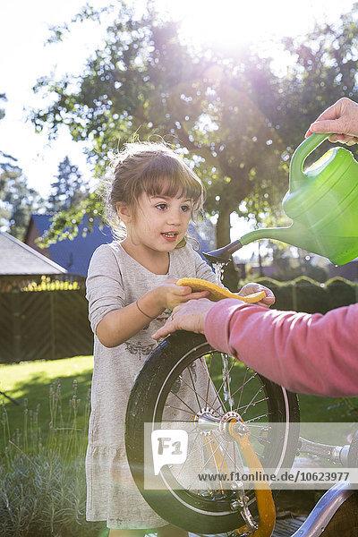 Mädchen und Frau beim Fahrrad waschen im Garten