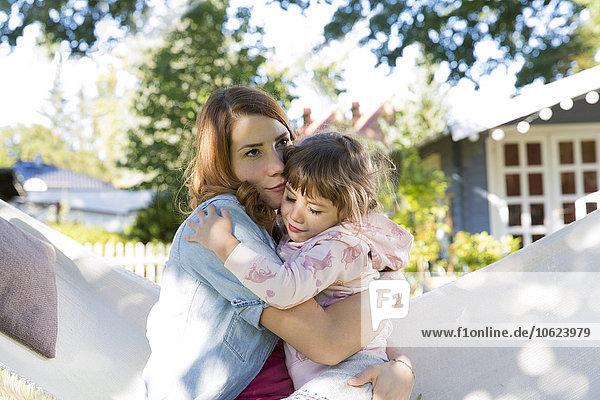 Mutter mit Tochter im Garten in der Hängematte