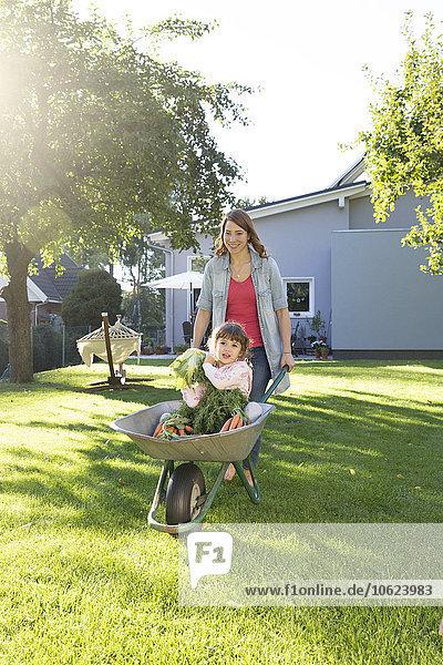 Mutter schiebende Tochter mit Karotten in Schubkarre im Garten