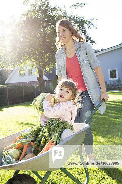 Mutter schiebt Tochter mit Gemüse in Schubkarre im Garten