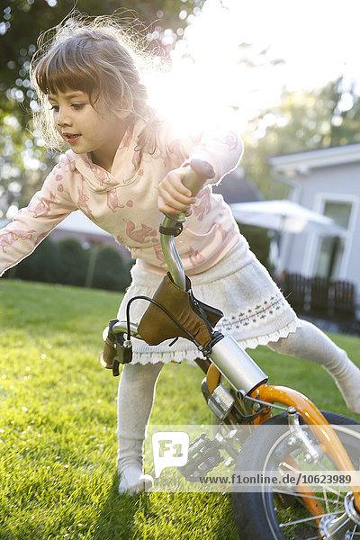 Mädchen auf dem Fahrrad im Garten