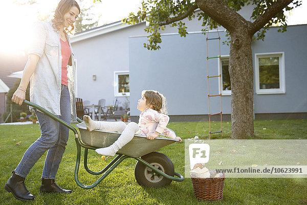 Mutter schiebt Tochter in Schubkarre im Garten
