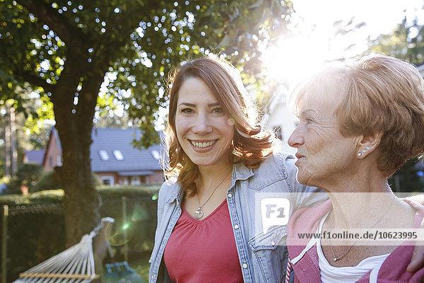 Porträt der lächelnden erwachsenen Tochter mit älterer Mutter im Garten