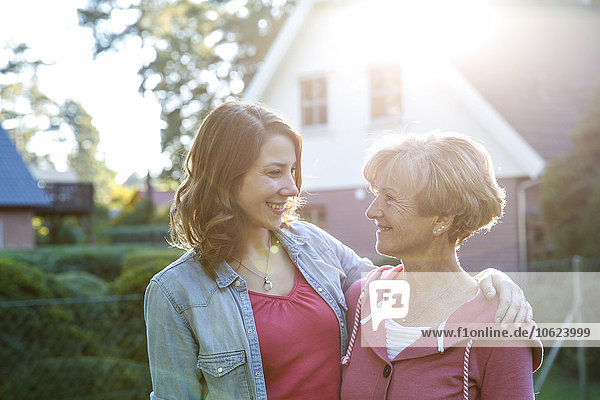 Smiling adult daughter with senior mother in garden